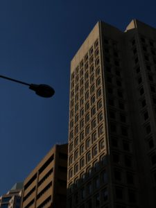 black street light near white concrete building during daytime